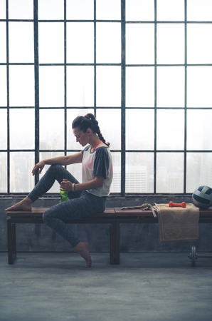 window bench: Relaxing and peaceful after a good yoga workout, a woman sits quietly on a wooden bench by the window in a loft gym.