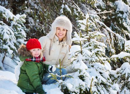 arbol geneal�gico: Invierno al aire libre puede ser de cuento de hadas-fabricante para los ni�os e incluso adultos. Madre y el ni�o al aire libre entre los abetos nevados feliz Foto de archivo