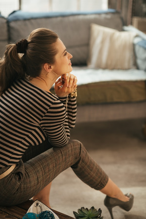 loft living: Side photo of stylish brunet woman sitting on small table infront of couch in loft living room and dreaming