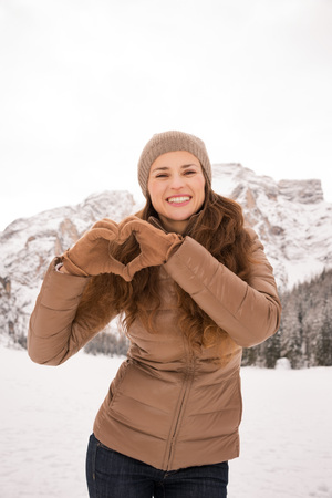 shaped hands: Energy-filling and exciting winter weekends in the mountains. Happy young woman showing heart shaped hands outdoors among snow-capped mountains