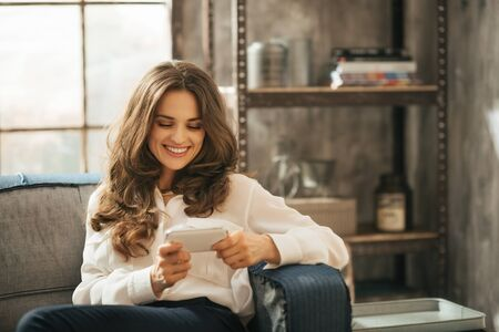 playing on divan: Stylish brunet woman is playing with smartphone sitting on divan in loft apartment