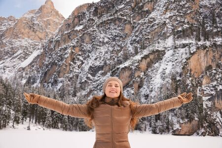Energy-filling and exciting winter weekends in the mountains. Portrait of happy young woman outdoors among snow-capped mountains rejoicing