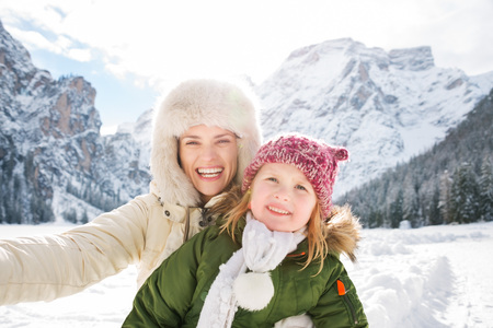 mam: Winter outdoors can be fairytale-maker for children or even adults. Smiling mother and child taking selfie outdoors in front of snowy mountains