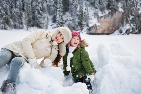 mother to be: Winter outdoors can be fairytale-maker for children or even adults. Portrait of smiling mother and child playing with the snow outdoors