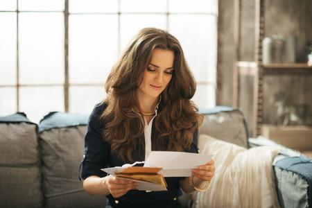 correspondencia: Mujer elegante joven con pelo marrón está sentado en el sofá y la lectura de la correspondencia en el loft Foto de archivo