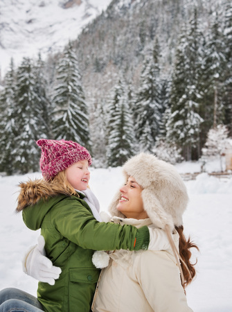 mother to be: Winter outdoors can be fairytale-maker for children or even adults. Happy mother and child playing outdoors in front of snowy mountains