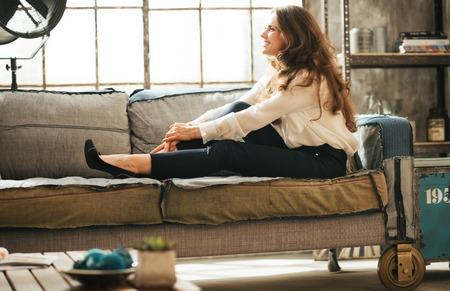 Lachende ontspannen jonge vrouw in een stijlvolle jurk is genieten van vrije tijd en ontspannen op de bank in de woonkamer van de zolder
