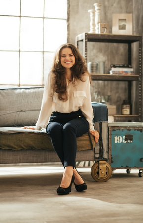 feet crossed: Smiling brunet woman in elegant clothing sitting on coach with crossed feet in loft apartment