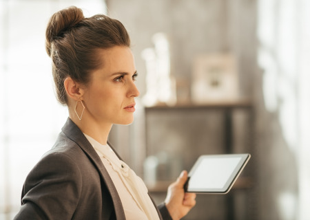 topicality: Successful modern business woman freshen up before work in her perfect loft apartment. Concentrated businesswoman holding tablet Stock Photo