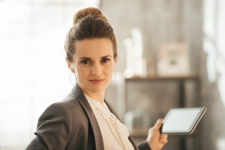 topicality: Successful modern business woman freshen up before work in her perfect loft apartment. Portrait of young business woman holding tablet