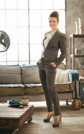 businesswoman suit: Successful modern business woman freshen up before work in her perfect loft apartment. Portrait of stylish smiling businesswoman in business suit Stock Photo