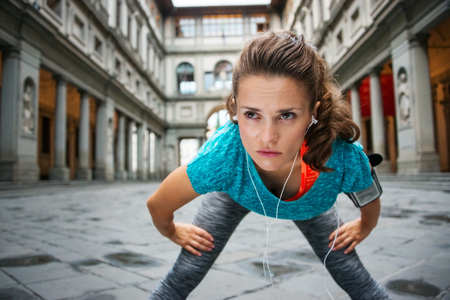 hometown: Now it is time to invest in your body and no matter you are at hometown or traveling. Young concentrated sportswoman is catching breath after outdoors workout next to Uffizi gallery in Florence Italy