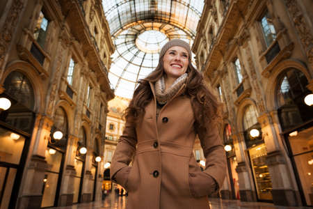 winter sales: Get ready to making your way through shopping addicted crowd. Huge winter sales in Milan just started. Portrait of smiling young woman in Galleria Vittorio Emanuele II looking into the distance