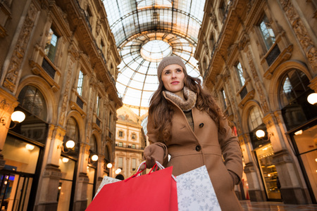 winter sales: Get ready to making your way through shopping addicted crowd. Huge winter sales in Milan just started. Vogue young woman with shopping bags in Galleria Vittorio Emanuele II looking into the distance Stock Photo