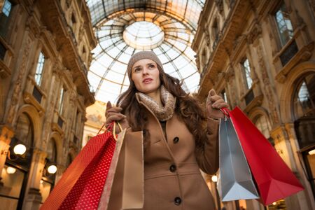 winter sales: Get ready to making your way through shopping addicted crowd. Huge winter sales in Milan just started. Young woman with shopping bags in Galleria Vittorio Emanuele II looking into the distance