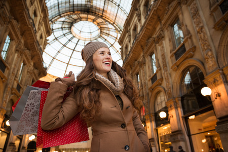 winter sales: Get ready to making your way through shopping addicted crowd. Huge winter sales in Milan just started. Smiling young woman with shopping bags in Galleria Vittorio Emanuele II looking on copy space