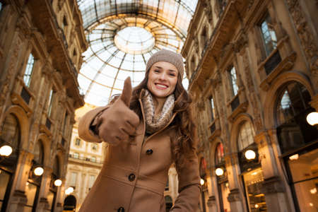 winter sales: Get ready to making your way through shopping addicted crowd. Huge winter sales in Milan just started. Portrait of happy young woman standing in Galleria Vittorio Emanuele II and showing thumbs up