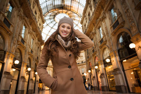 winter sales: Get ready to making your way through shopping addicted crowd. Huge winter sales in Milan just started. Portrait of smiling young woman standing in Galleria Vittorio Emanuele II Stock Photo