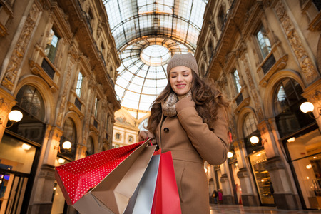 winter sales: Get ready to making your way through shopping addicted crowd. Huge winter sales in Milan just started. Happy young woman with shopping bags standing in Galleria Vittorio Emanuele II Stock Photo