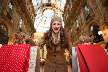 winter sales: Get ready to making your way through shopping addicted crowd. Huge winter sales in Milan just started. Smiling young woman in Galleria Vittorio Emanuele II showing shopping bags Stock Photo