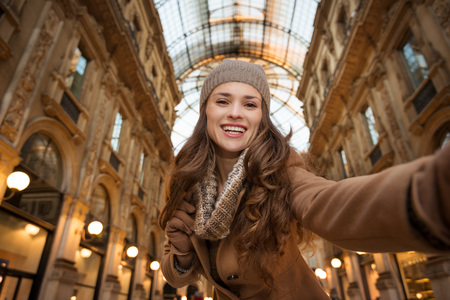 winter sales: Get ready to making your way through shopping addicted crowd. Huge winter sales in Milan just started. Smiling young woman shopper taking selfie in Galleria Vittorio Emanuele II