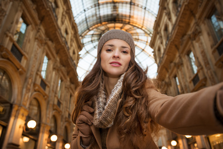winter sales: Get ready to making your way through shopping addicted crowd. Huge winter sales in Milan just started. Glamour young woman shopper taking selfie in Galleria Vittorio Emanuele II