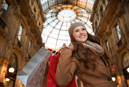 winter sales: Get ready to making your way through shopping addicted crowd. Huge winter sales in Milan just started. Smiling young woman with shopping bags in Galleria Vittorio Emanuele II looking into the distance