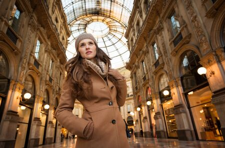 winter sales: Get ready to making your way through shopping addicted crowd. Huge winter sales in Milan just started. Portrait of young woman shopper in Galleria Vittorio Emanuele II looking into the distance