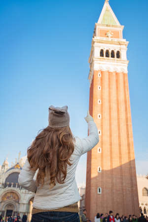 anonym: Take classical tourist enjoyment in Venice, Italy - wander over San Marco square, chase pigeons and take photos. Seen from behind young woman pointing on bell tower of St Marks Basilica