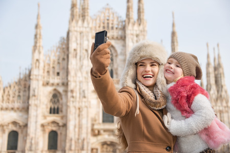 hang out: Why not to hang out in Italian fashion capital Milan on winter holidays with family. Happy mother and daughter taking selfie in front of Duomo