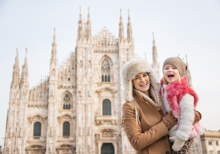 mam: Why not to hang out in Italian fashion capital Milan on winter holidays with family. Portrait of smiling mother and daughter in front of Duomo Stock Photo