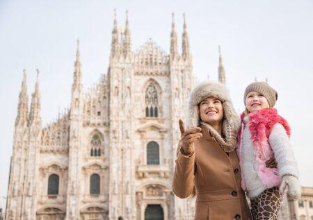 familia en la iglesia: ¿Por qué no pasar un rato en capital de la moda italiana de Milán en vacaciones de invierno con la familia. Madre feliz que muestra algo a la hija mientras está de pie frente a Catedral