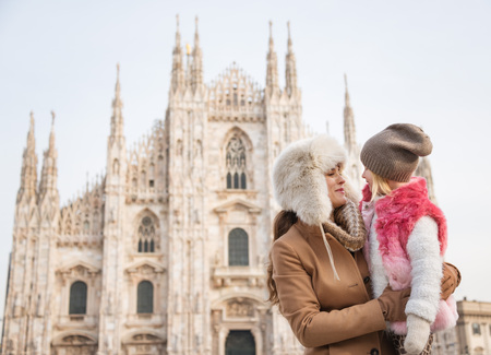 hang out: Why not to hang out in Italian fashion capital Milan on winter holidays with family. Mother and daughter in front of Duomo spending fun time sightseeing Milan