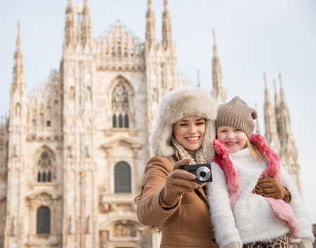 hang out: Why not to hang out in Italian fashion capital Milan on winter holidays with family. Smiling mother and daughter looking on photos in the digital camera in front of Duomo Stock Photo