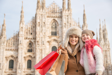 hang out: Why not to hang out in Italian fashion capital Milan on winter holidays with family. Portrait of smiling mother and daughter with shopping bags in front of Duomo Stock Photo