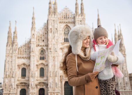 hang out: Why not to hang out in Italian fashion capital Milan on winter holidays with family. Happy mother and daughter looking on map while standing in front of Duomo