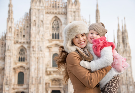 hang out: Why not to hang out in Italian fashion capital Milan on winter holidays with family. Portrait of happy mother and daughter in front of Duomo