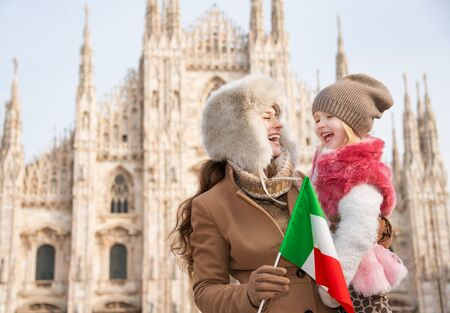 Why not to hang out in Italian fashion capital Milan on winter holidays with family. Smiling mother and daughter holding Italian flag in front of Duomo Stock Photo - 51874950