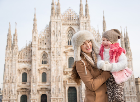 hang out: Why not to hang out in Italian fashion capital Milan on winter holidays with family. Portrait of laughing mother and daughter in front of Duomo