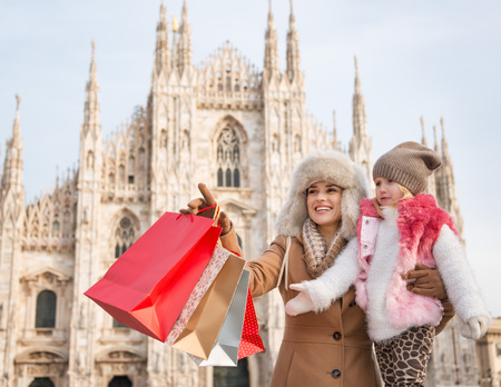 why not: Why not to hang out in Italian fashion capital Milan on winter holidays with family. Mother with shopping bags pointing on something to daughter while in front of Duomo