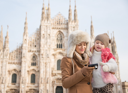 hang out: Why not to hang out in Italian fashion capital Milan on winter holidays with family. Mother and daughter looking on photos in the digital camera in front of Duomo
