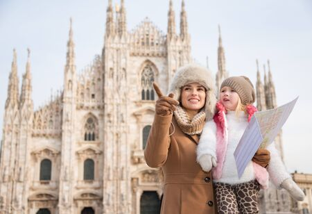 hang out: Why not to hang out in Italian fashion capital Milan on winter holidays with family. Mother with map pointing on something to daughter while in front of Duomo