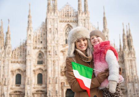 familia en la iglesia: ¿Por qué no pasar un rato en capital de la moda italiana de Milán en vacaciones de invierno con la familia. madre e hija felices con la bandera italiana de pie frente a Catedral