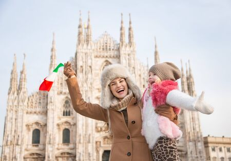 hang out: Why not to hang out in Italian fashion capital Milan on winter holidays with family. Happy mother and daughter with Italian flag rejoicing in front of Duomo