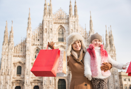 hang out: Why not to hang out in Italian fashion capital Milan on winter holidays with family. Portrait of happy mother and daughter with shopping bags in front of Duomo