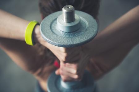 健身: 身心鍛煉的閣樓健身室。健身女子抱著腦袋後面啞鈴。特寫