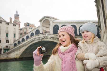 winter photos: Modern family taking a winter break to enjoy inspirational adventure in Venice, Italy. Happy mother and daughter taking photos while standing in front of Rialto Bridge Stock Photo