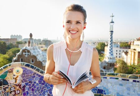 Refreshing promenade in unique Park Guell style in Barcelona, Spain. Happy young woman holding tourist guide and listening audioguide while in Park Guell, Barcelona, Spain