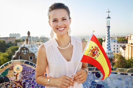 catalunia: Refreshing promenade in unique Park Guell style in Barcelona, Spain. Portrait of smiling young woman tourist with Spain flag in Park Guell, Barcelona, Spain