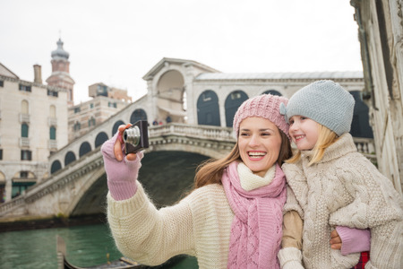 winter photos: Modern family taking a winter break to enjoy inspirational adventure in Venice, Italy. Mother and daughter taking photos while standing in front of Ponte di Rialto